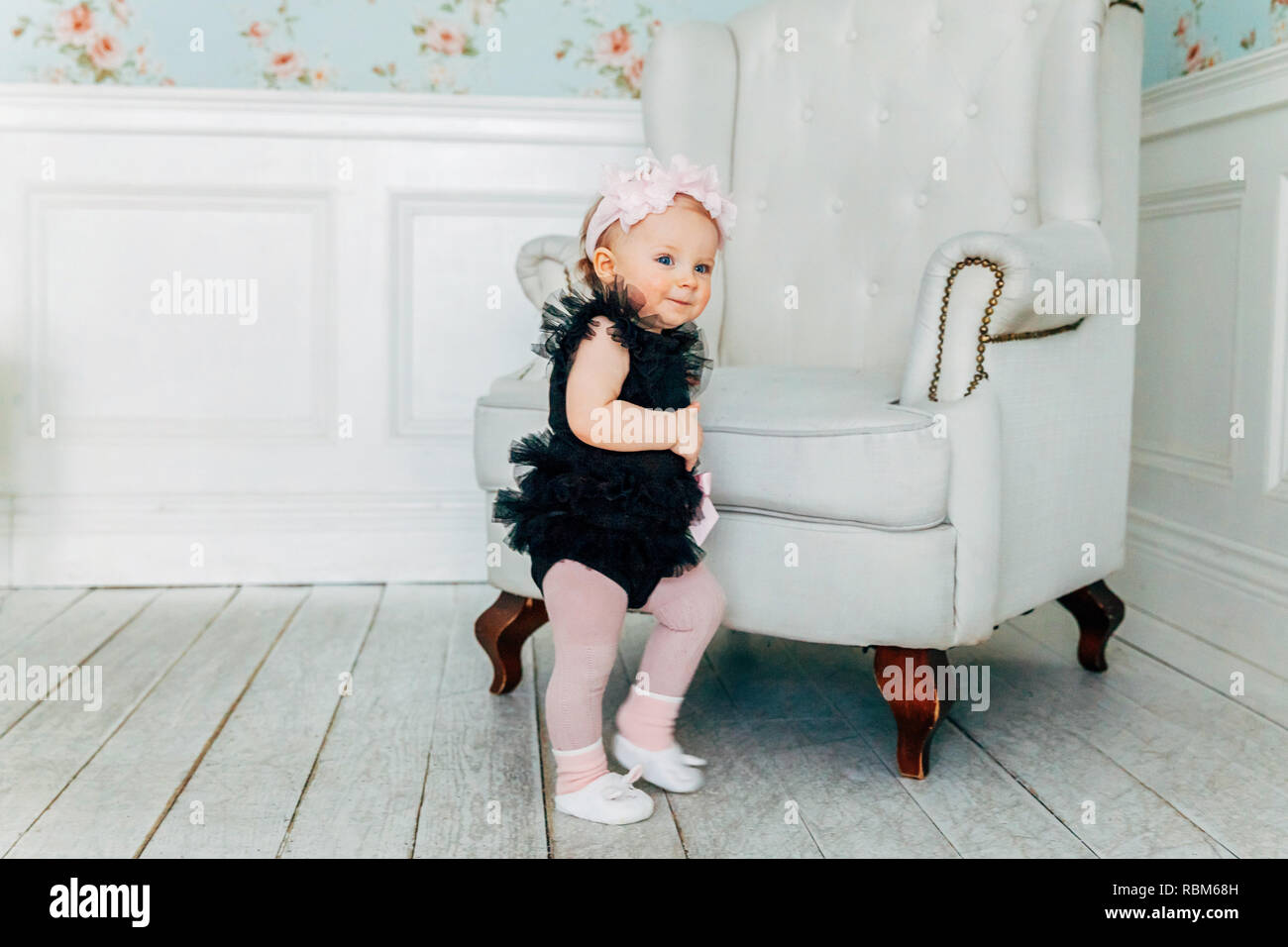 Little baby girl one year old wearing spring wreath standing ...