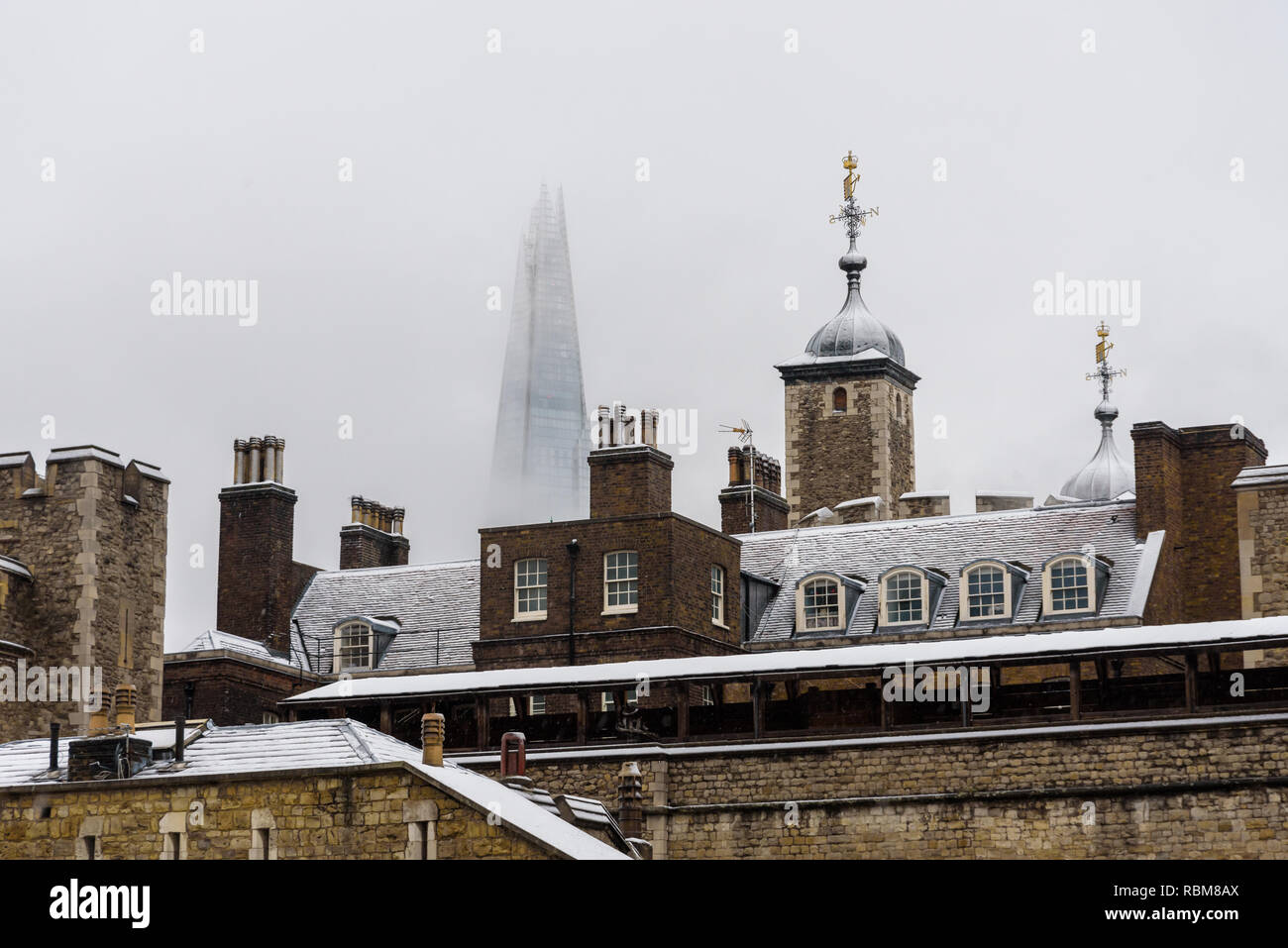 Snow in London. The roofs of Tower of London covered in fresh white snow. In the background the Shard, the tallest skyscraper in Europe. - Stock Image