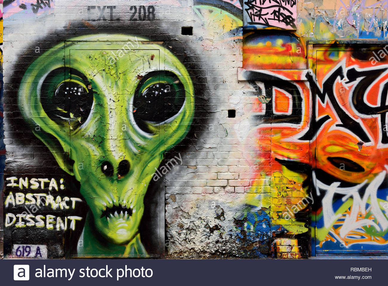 Alley street art painting, mural of an extraterrestial alien being with large eyes. - Stock Image
