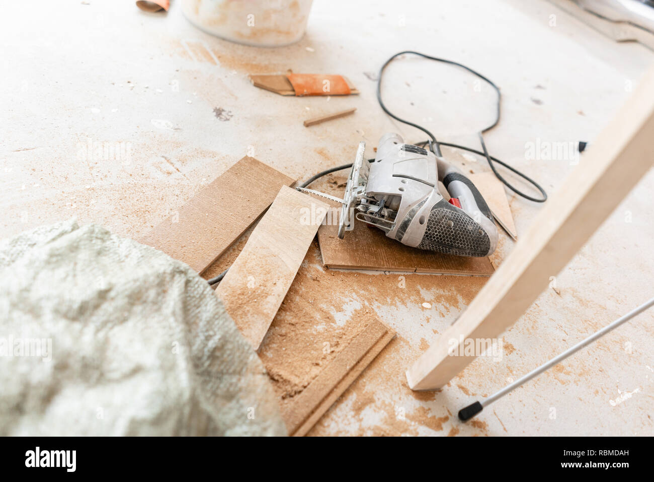 Close-up tools for cuts the laminate Board with an electrofret saw. installing new wooden laminate flooring. concept of repair in house. - Stock Image