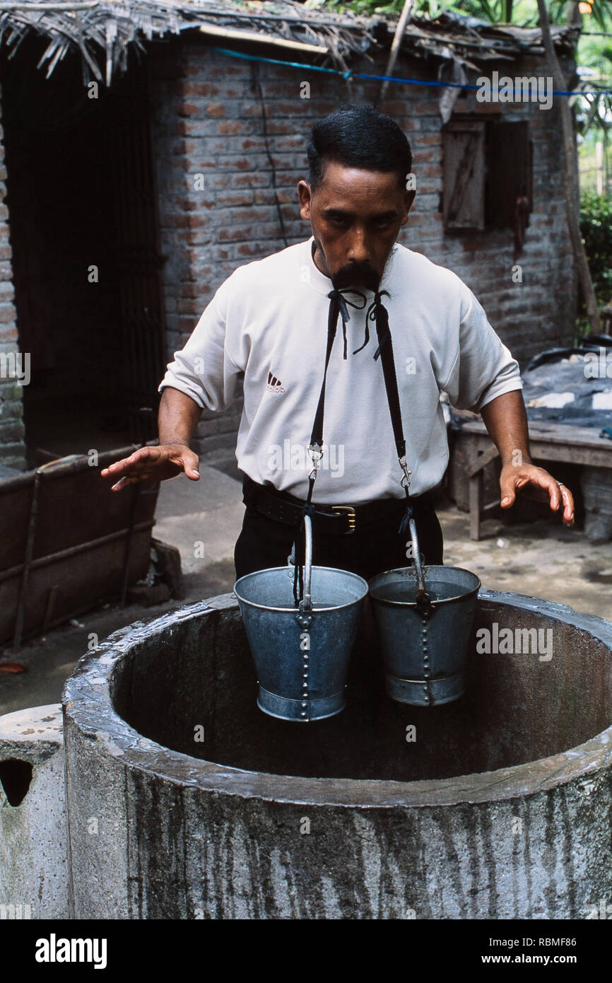 Sailendra Nath Roy holding buckets of water with his moustache, India, Asia - Stock Image
