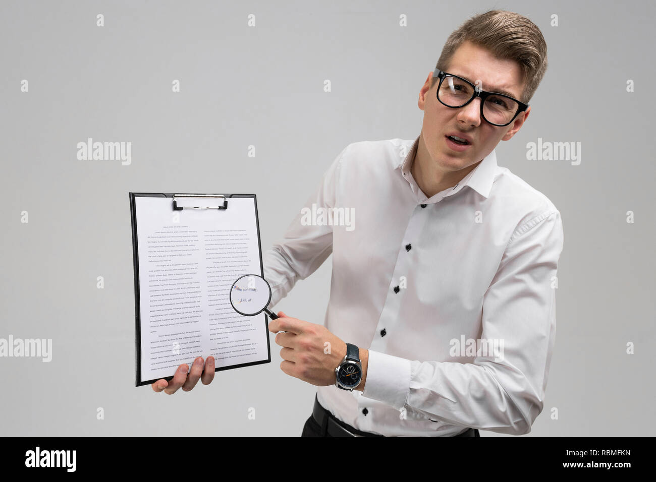 Young man in glasses with insurance and magnifier in hand isolated on white background - Stock Image