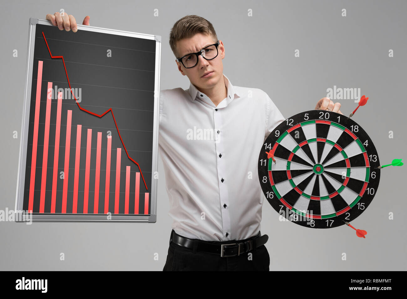 Young man in glasses holding a Board with falling statistics and Darts isolated on white background - Stock Image