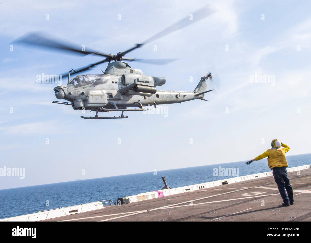 190102-N-PH222-1083 ARABIAN SEA (Jan. 2, 2018) Aviation Boatswain's Mate (Handling) Airman Eddie De La Cruz, from Garden Grove, Calif., salutes a AH–1Z Viper helicopter, attached to Marine Medium Tiltrotor Squadron (VMM) 166 (Reinforced), from the flight deck of the San Antonio-class amphibious transport dock ship USS Anchorage (LPD 23) while on a deployment of the Essex Amphibious Ready Group (ARG) and 13th Marine Expeditionary Unit (MEU). The Essex ARG/13th MEU is flexible and persistent Navy-Marine Corps team deployed to the U.S. 5th Fleet area of operations in support of naval operations t - Stock Image