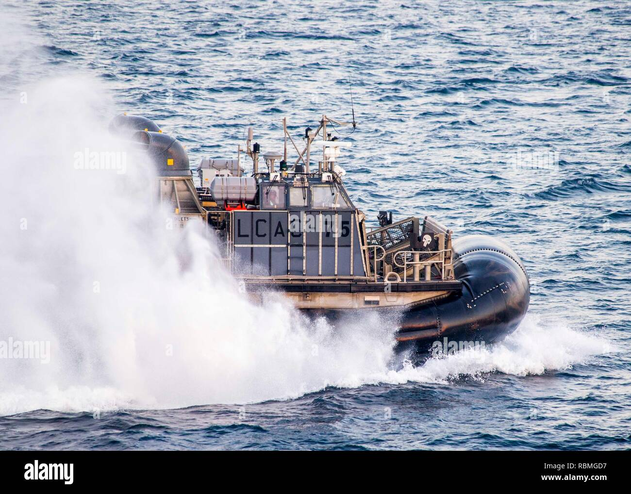 190104-N-PH222-1237 ARABIAN SEA (January 4, 2019) Landing Craft Air Cushion (LCAC) 75, attached to Assault Craft Unit 5, embarked aboard the San Antonio-class amphibious transport dock ship USS Anchorage (LPD 23), transits the Arabian Sea while on a deployment of the Essex Amphibious Ready Group (ARG) and 13th Marine Expeditionary Unit (MEU). The Essex ARG/13th MEU is flexible and persistent Navy-Marine Corps team deployed to the U.S. 5th Fleet area of operations in support of naval operations to ensure maritime stability and security in the Central Region, connecting the Mediterranean and the - Stock Image