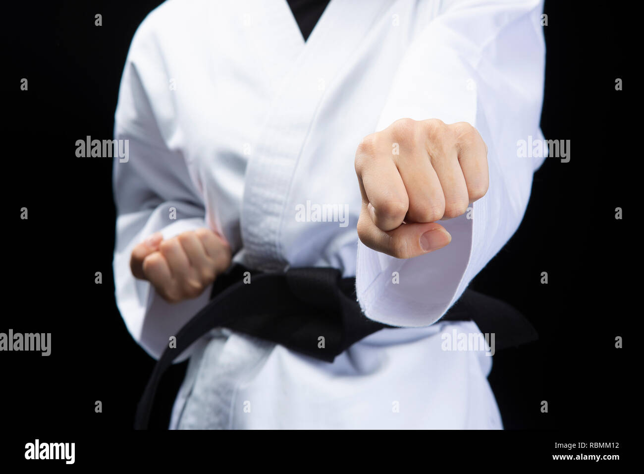 Fist of woman in karate suit on black background - Stock Image
