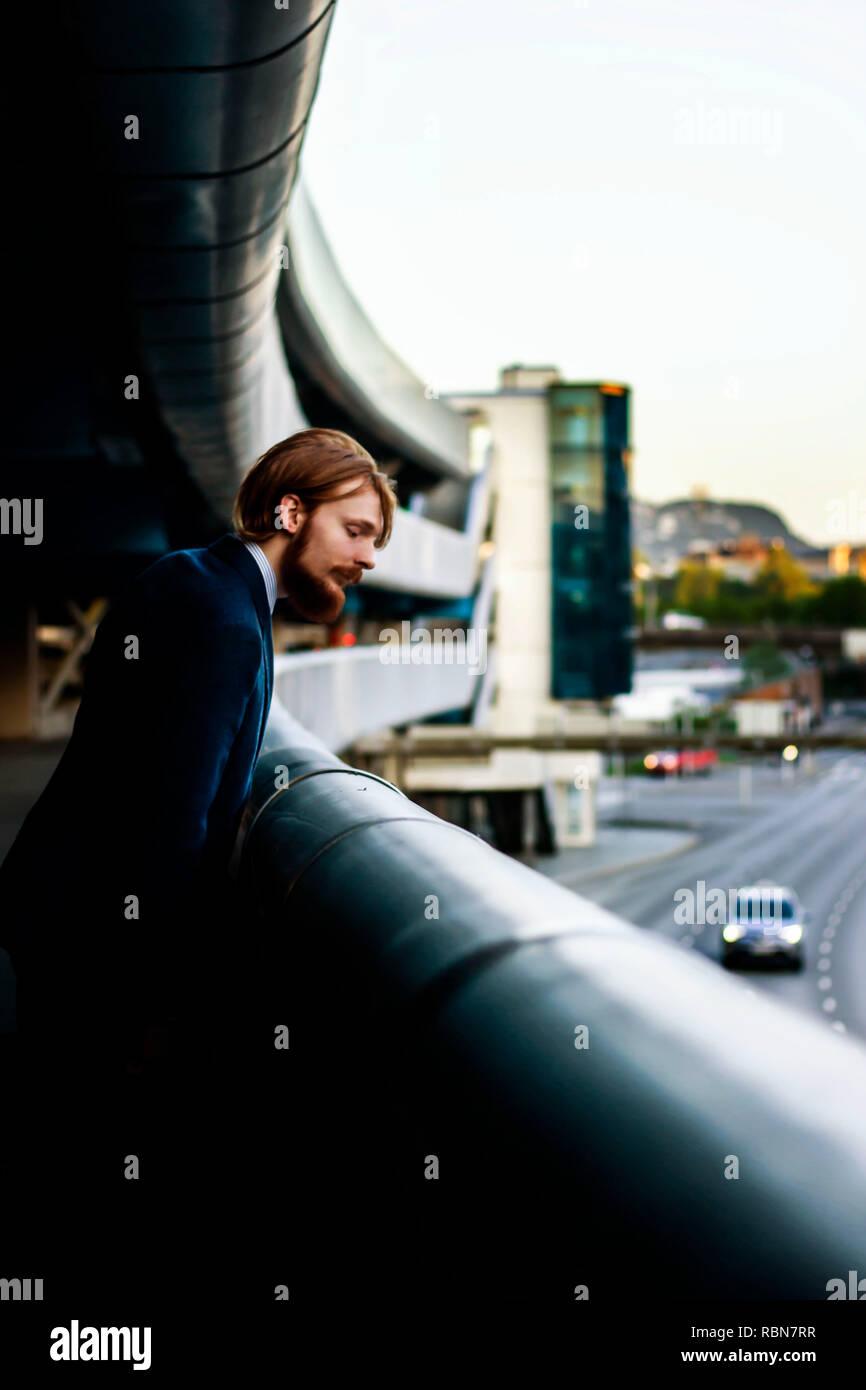a man looking down at cars - Stock Image