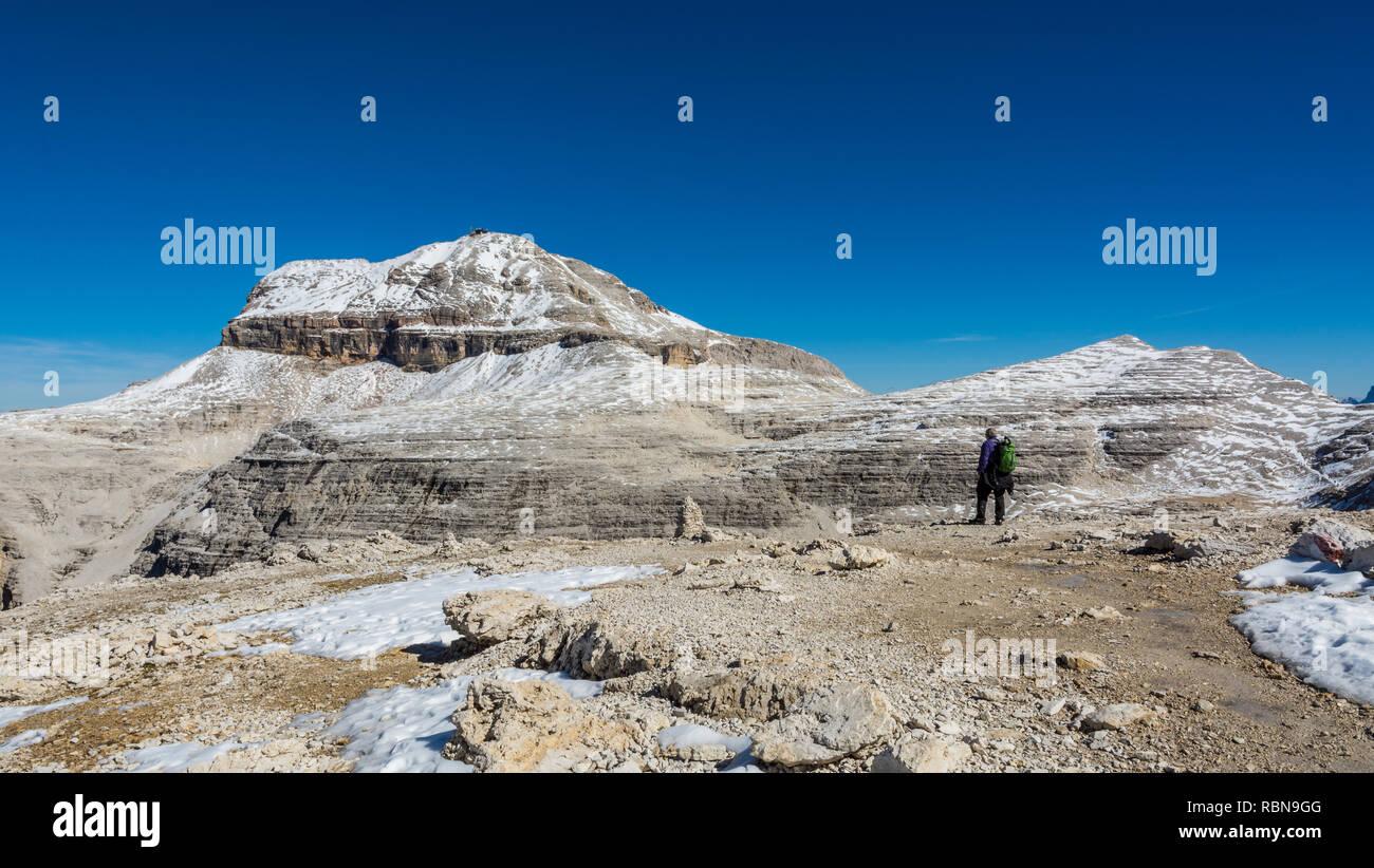 Tourist on the rock of the Sass Pordoi. View towards Piz Boe Mountain, Sella Group, Dolomites, Trentino province, Italy. Stock Photo
