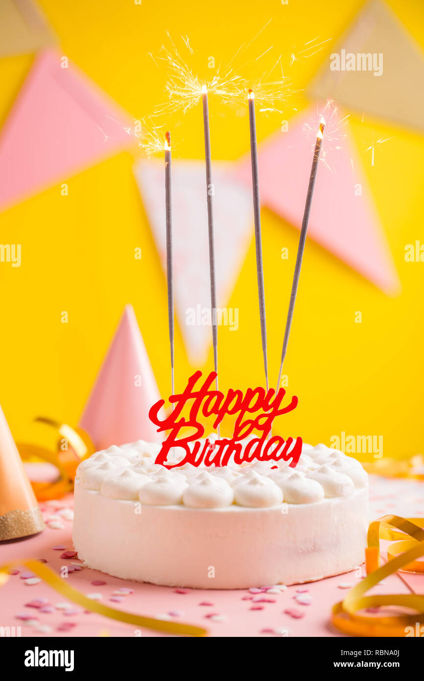 Happy Colorful Birthday Cake With Sparklers And Party Accessorizes Yellow Background Closeup