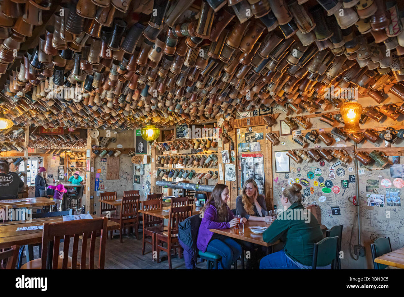 Marshall, Michigan - Thousands of mugs hang from the ceiling and walls of the tap room at the Dark Horse Brewery. Customers buy their own ceramic mugs - Stock Image