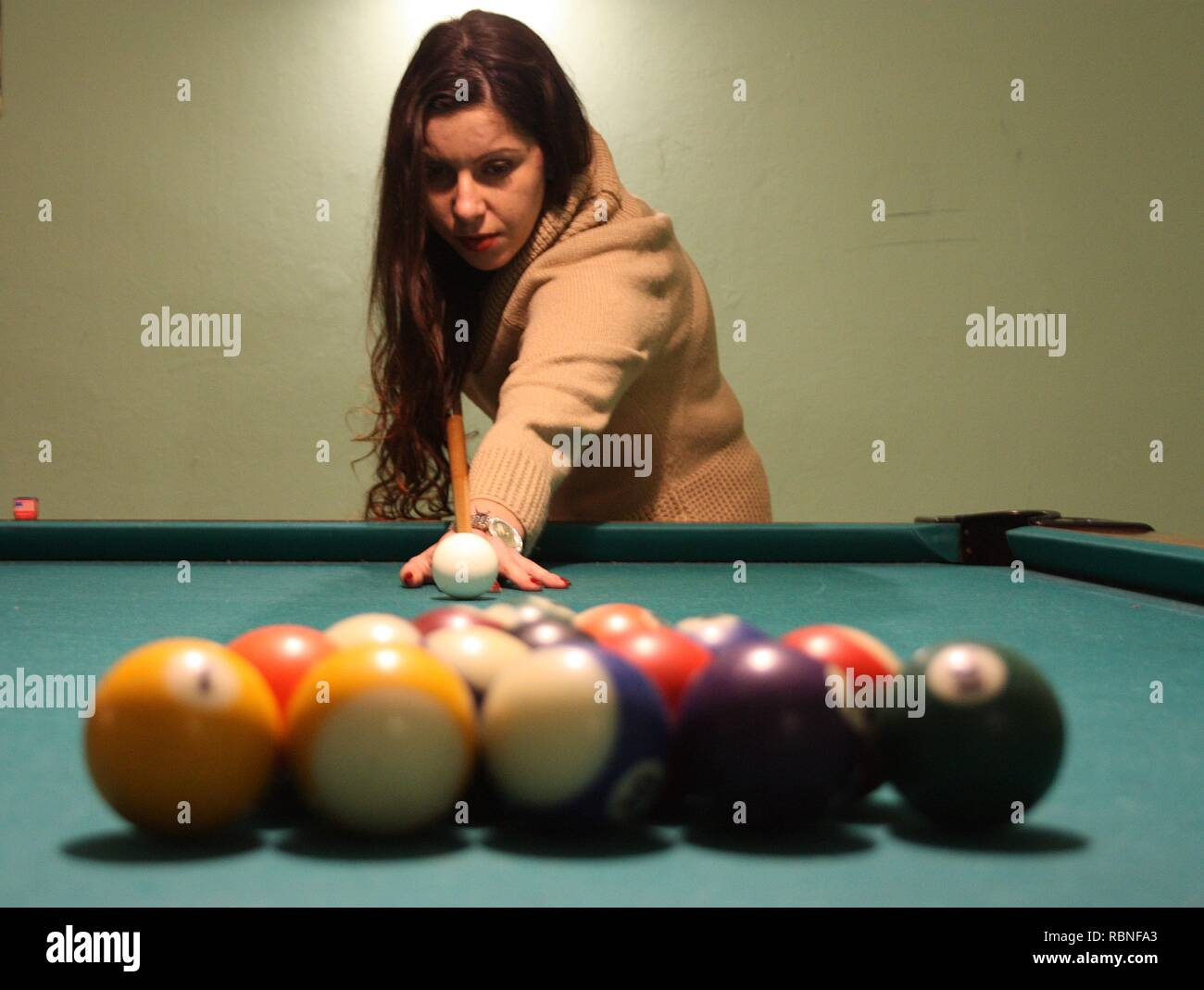 brown-haired caucasian girl plays billiards. the person is attentive to the game, the cue, the balls and the holes - Stock Image