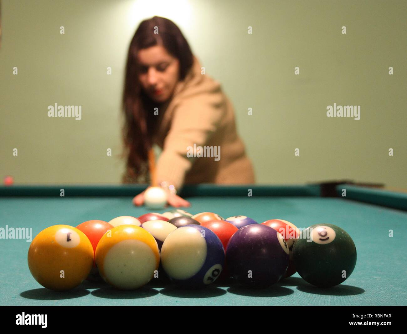 brown-haired caucasian girl plays billiards. the person is attentive to the game, the cue, the balls and the holes Stock Photo