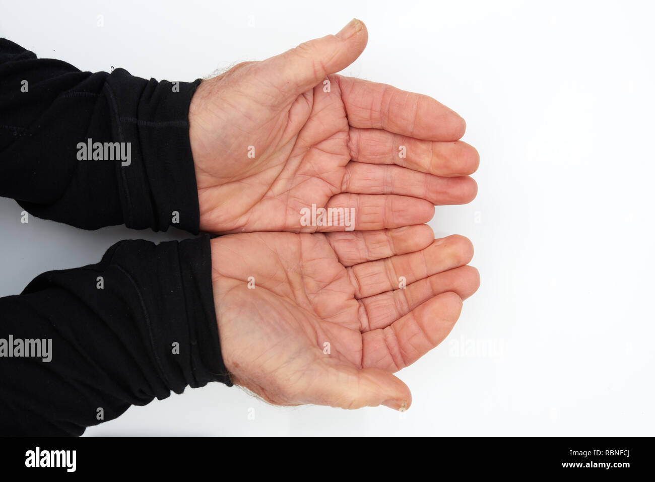 Two hands of an old man cupped in anticipation of receiving something - Stock Image