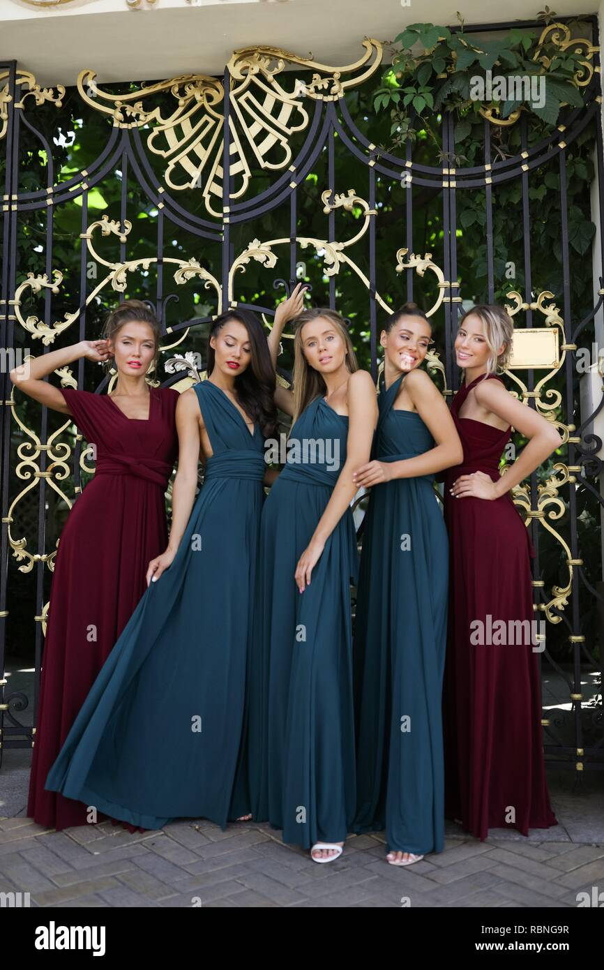 Five bridesmaids in the amazing red and green dresses posing near the gates, party,