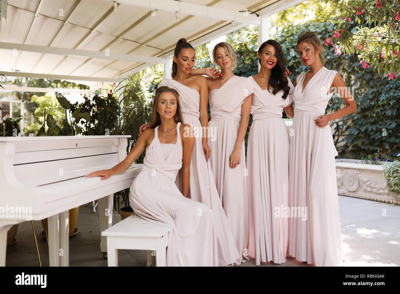 Tender feminine ladies in the light pink dresses standing