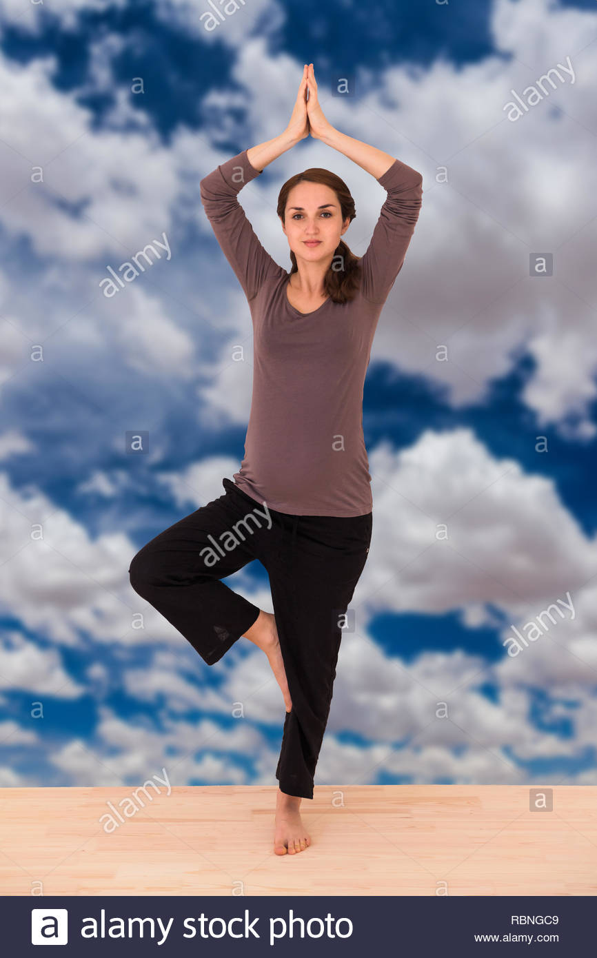 Pregnant girl doing yoga against a cloudy sky - Stock Image