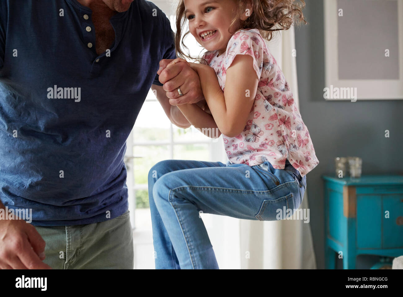 Girl jumping up and holding dad's hand at home, mid section - Stock Image