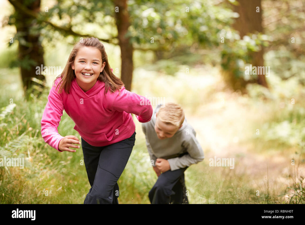 Two children walking in a forest amongst greenery smiling at camera, front view, focus on foreground - Stock Image