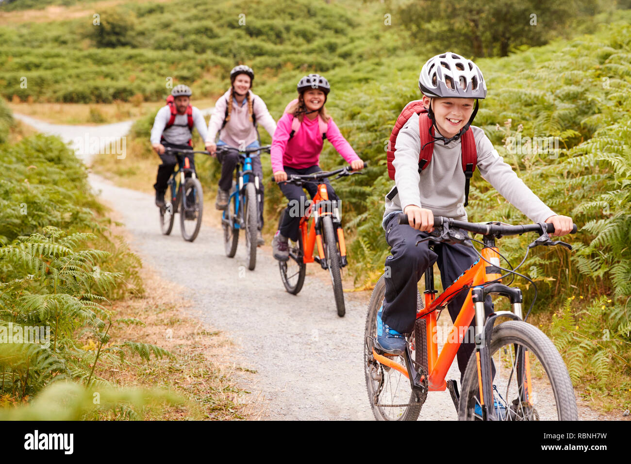 Pre-teen boy riding mountain bike with his sister and parents during a family camping trip, close up - Stock Image