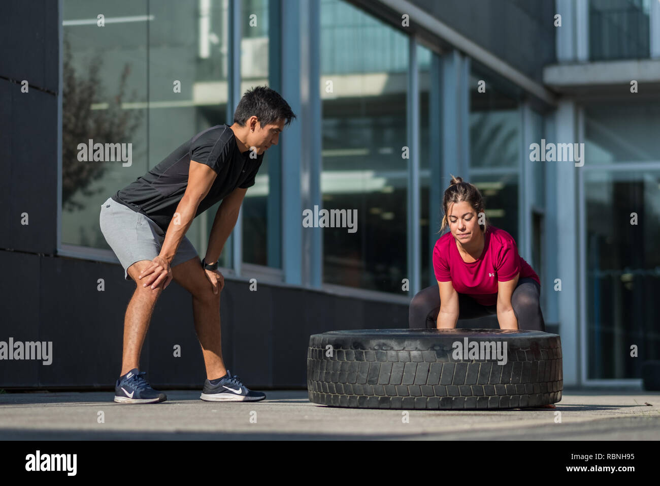 Personal trainer supervising young woman performing a tire flip over - Stock Image