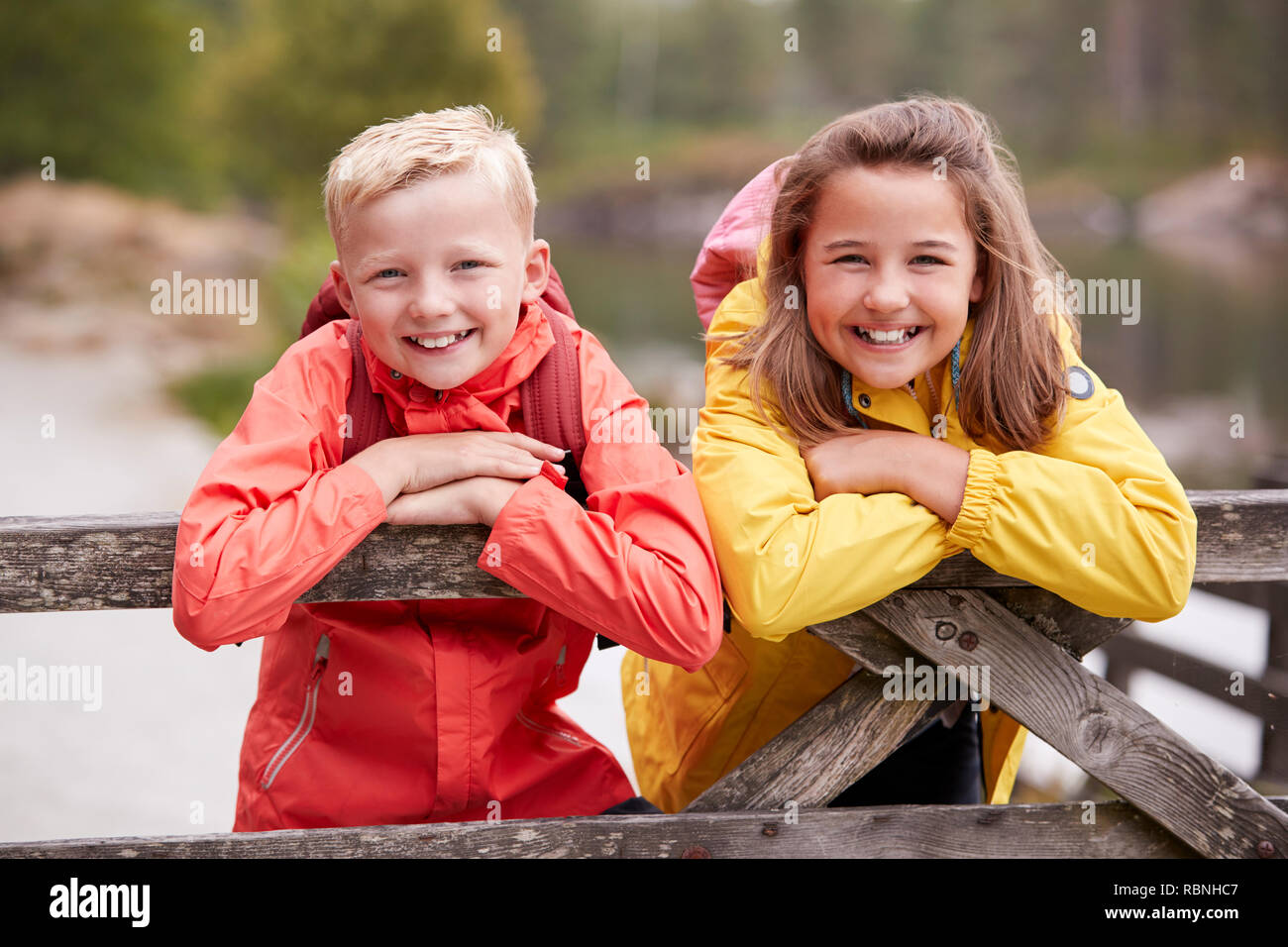 Two children leaning on a wooden fence in the countryside smiling to camera, close up - Stock Image