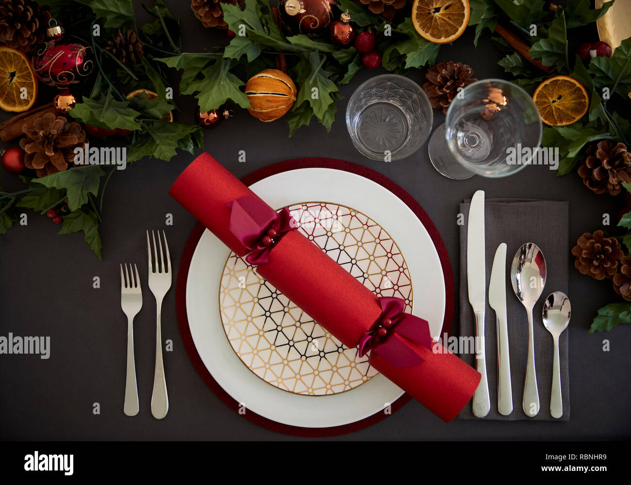 Christmas table setting with a red Christmas cracker arranged on a plate and green and red table decorations, overhead view Stock Photo