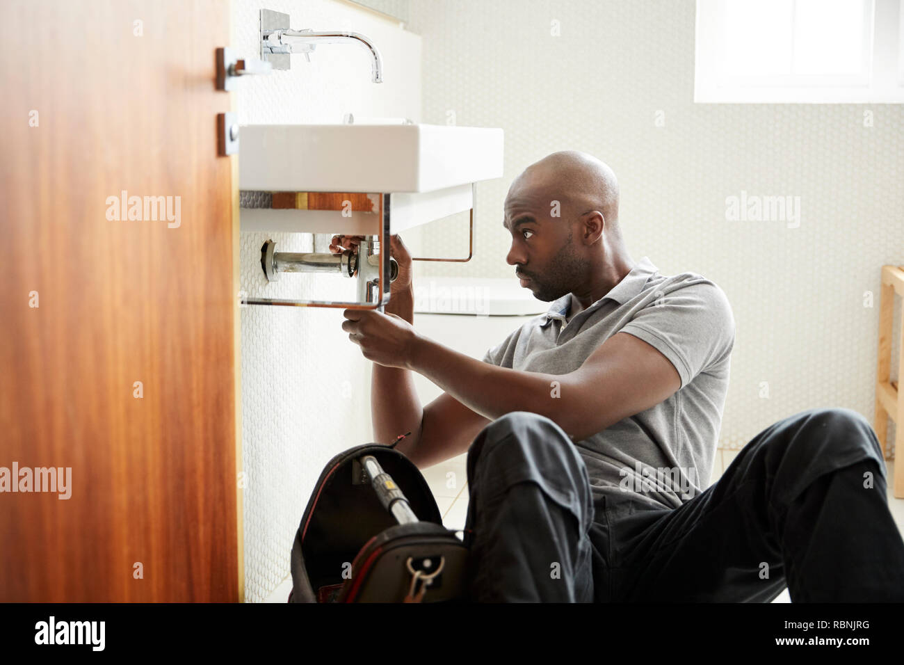 Young black male plumber sitting on the floor fixing a bathroom sink, seen from doorway - Stock Image