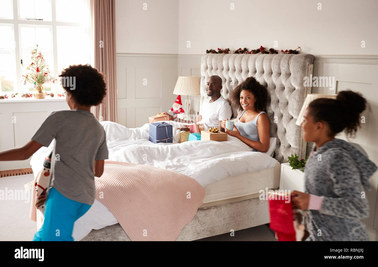 Excited children running into their parents' bedroom on Christmas morning, parents sitting up in bed Stock Photo