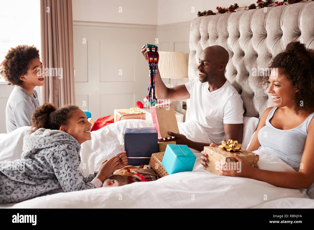 Dad sitting up in bed opening a gift on Christmas morning watched by his family, close up - Stock Image