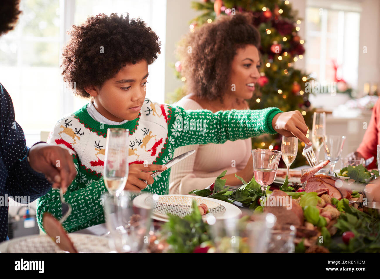 Tween black boy serving himself roast turkey sitting at the Christmas dinner table with his family, side view - Stock Image