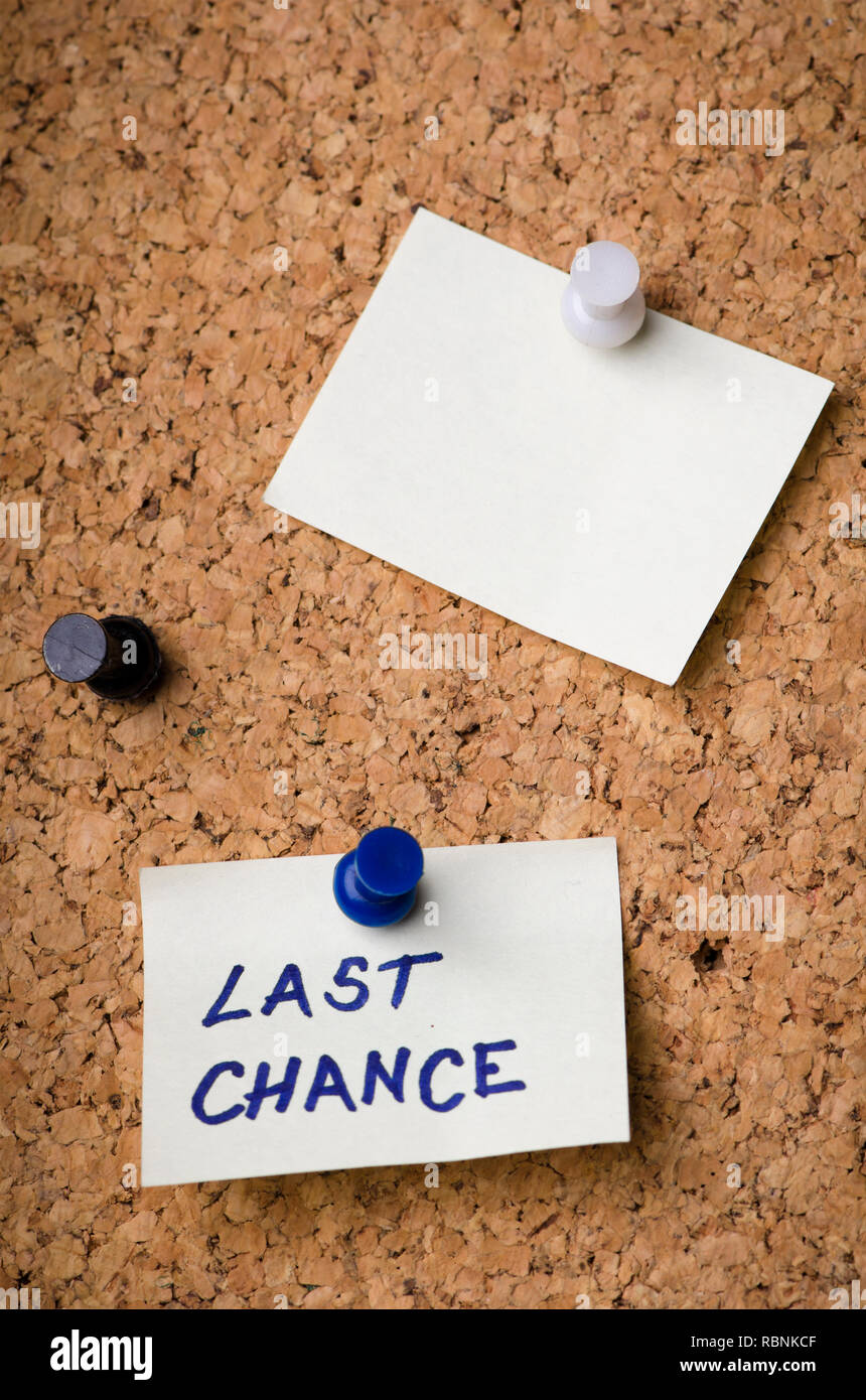 Last chance message on sticker note pin on cork office board. Reminder sign  written on card. Business concept. - Stock Image