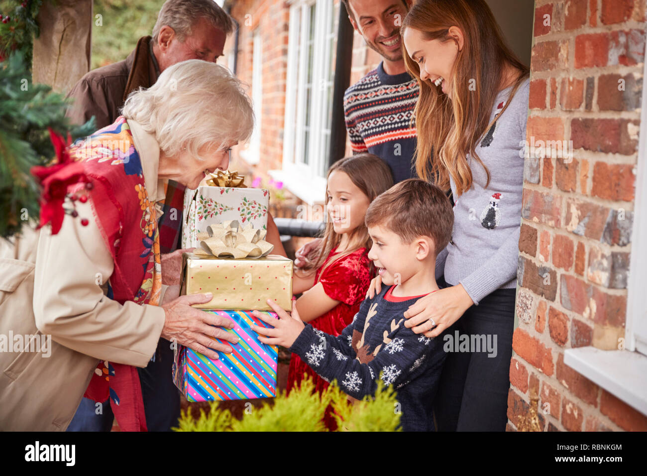 Grandparents Being Greeted By Family As They Arrive For Visit On Christmas Day With Gifts - Stock Image