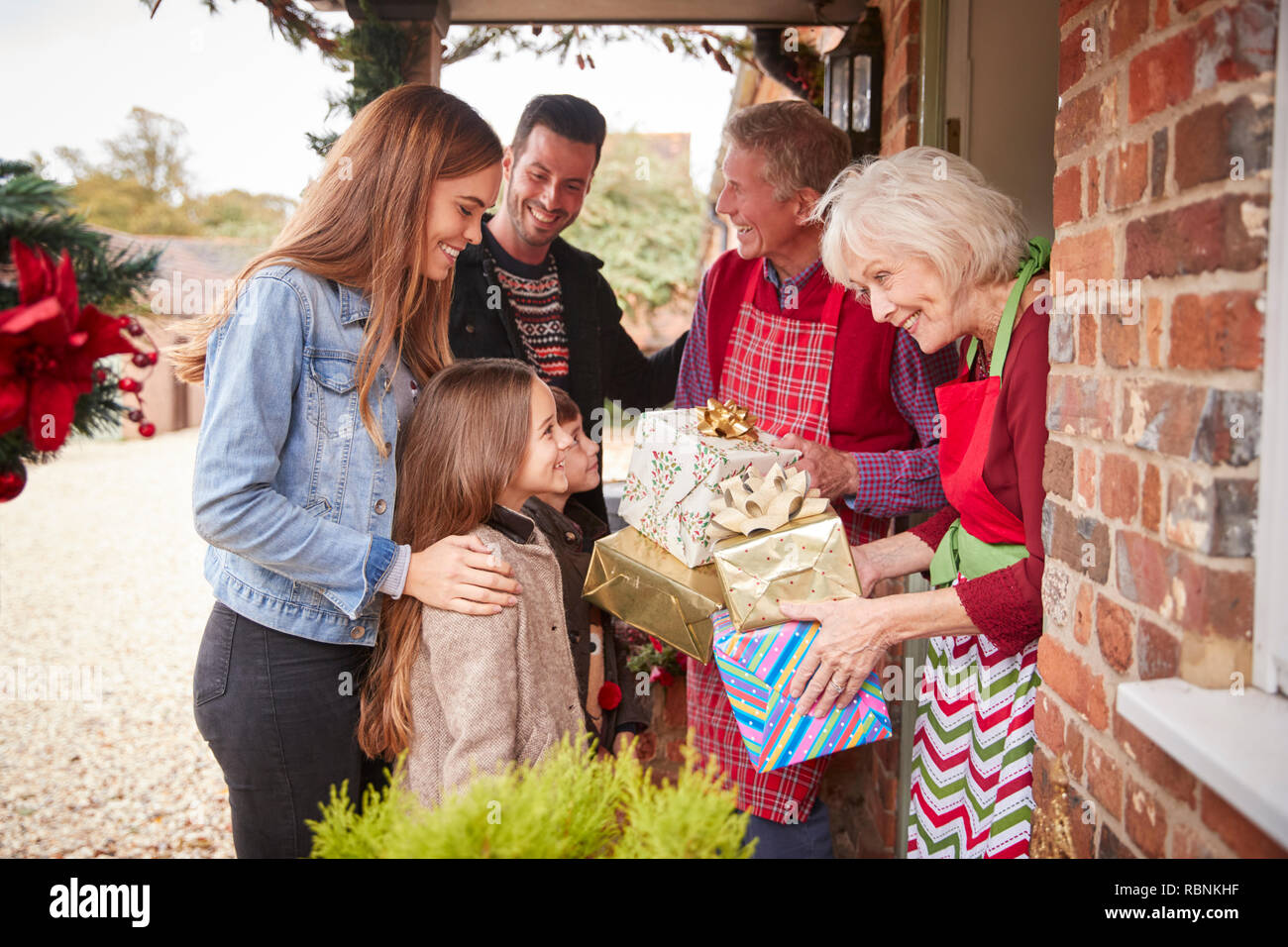 Family Being Greeted By Grandparents As They Arrive For Visit On Christmas Day With Gifts - Stock Image