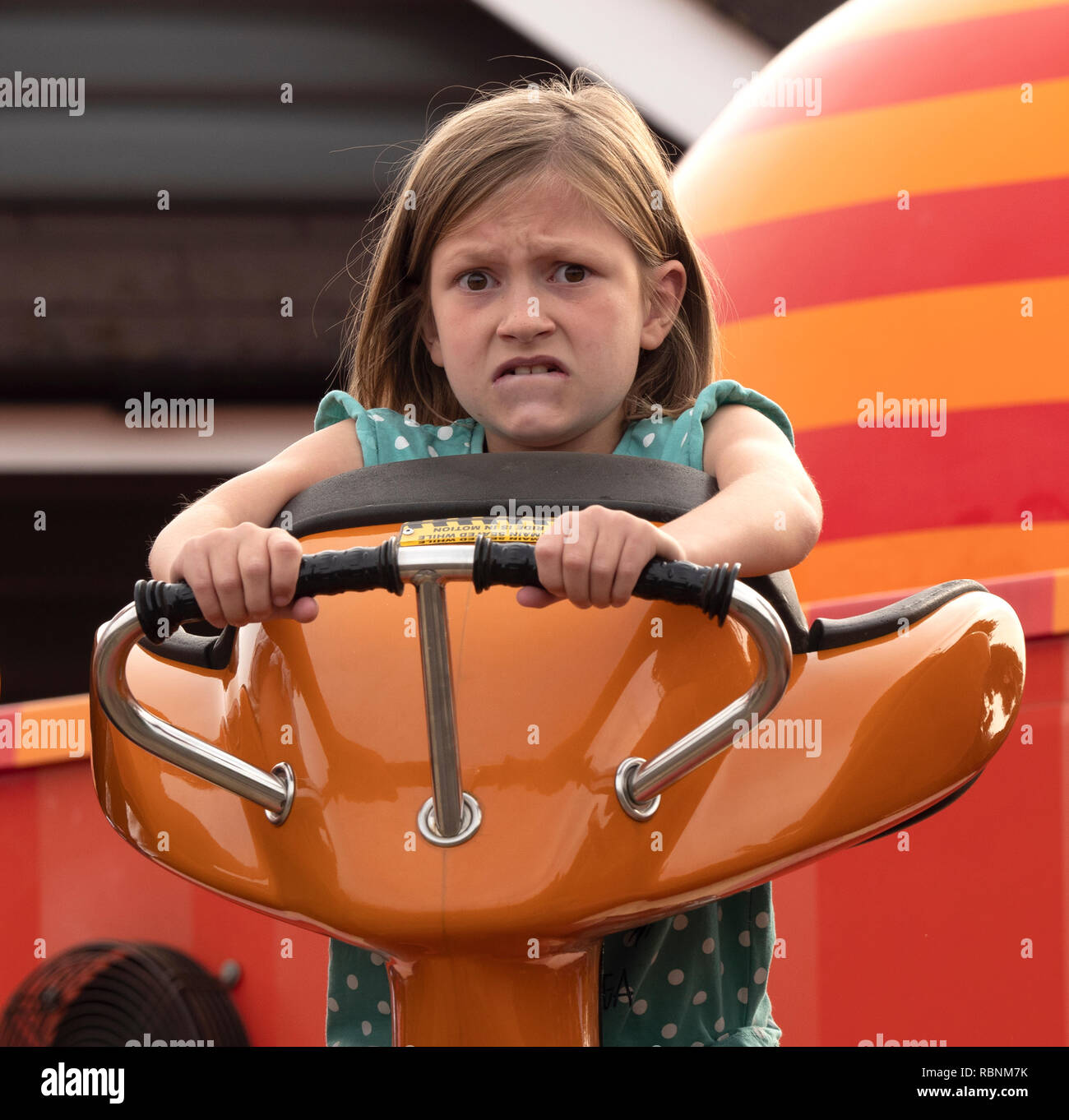 7 year old girl worried about pleasure park ride. - Stock Image