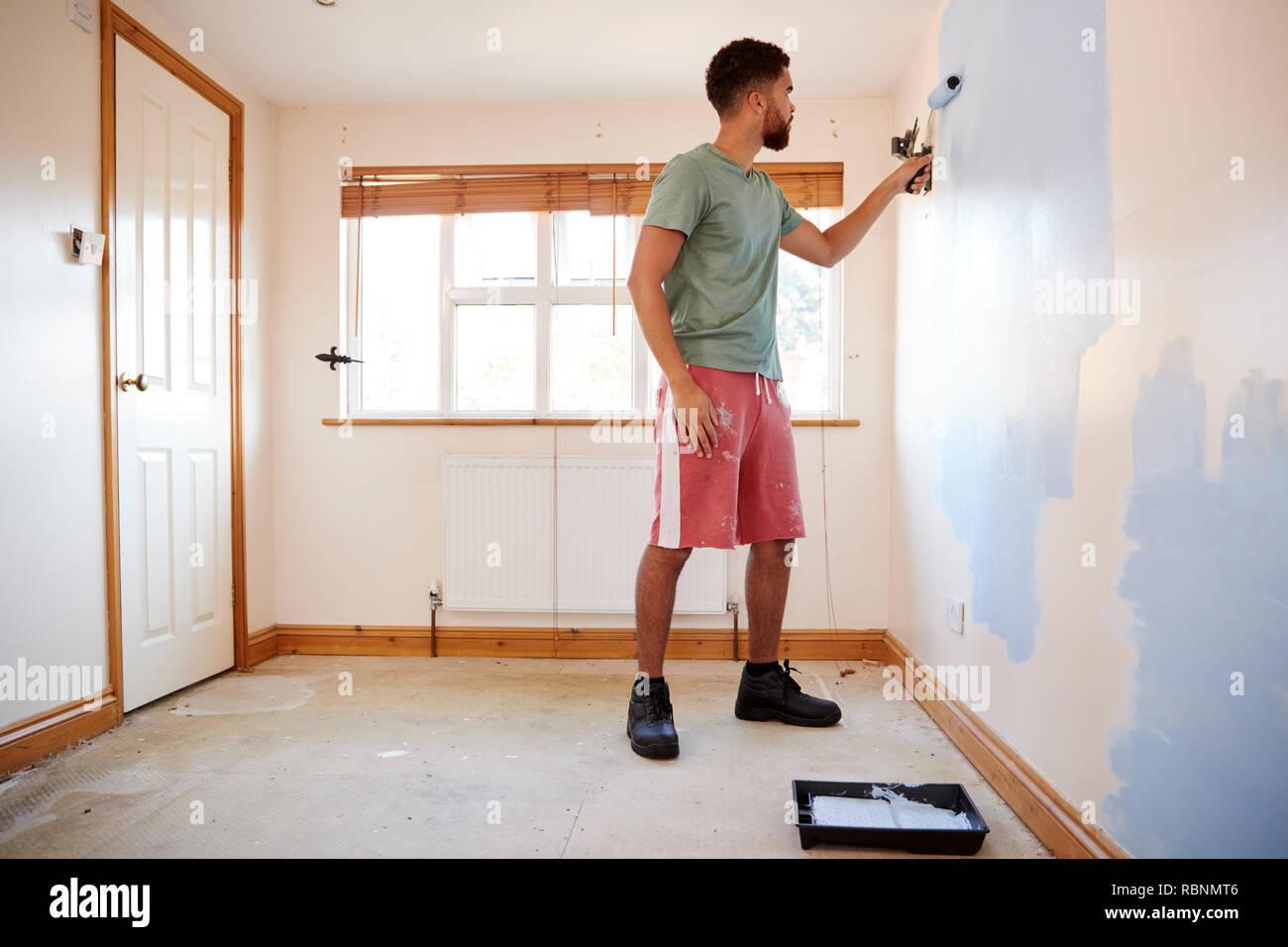Man Decorating Room In New Home Painting Wall Stock Photo: 230973350
