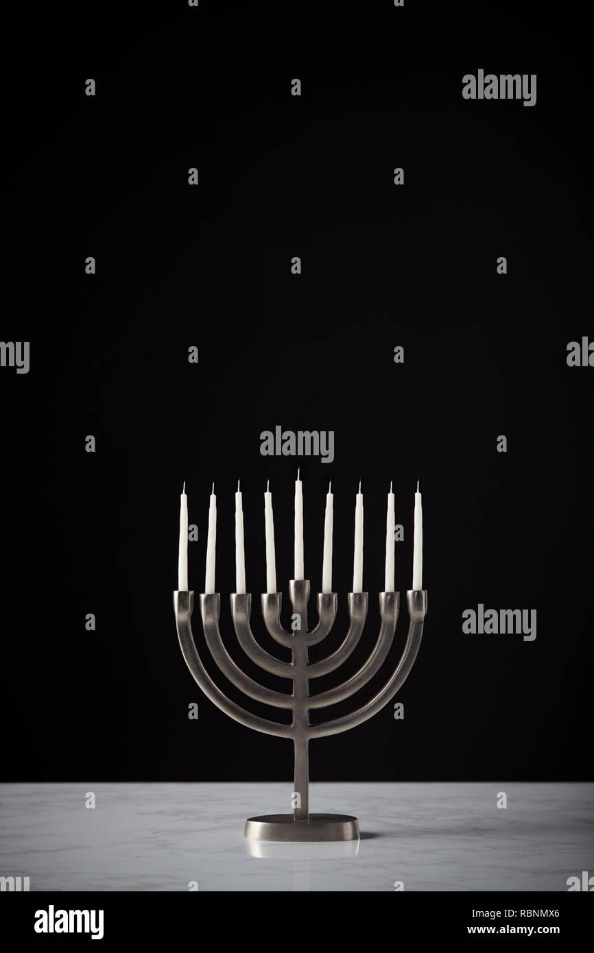 Metal Hanukkah Menorah With Unlit Candles On Marble Surface Against Black Studio Background Stock Photo