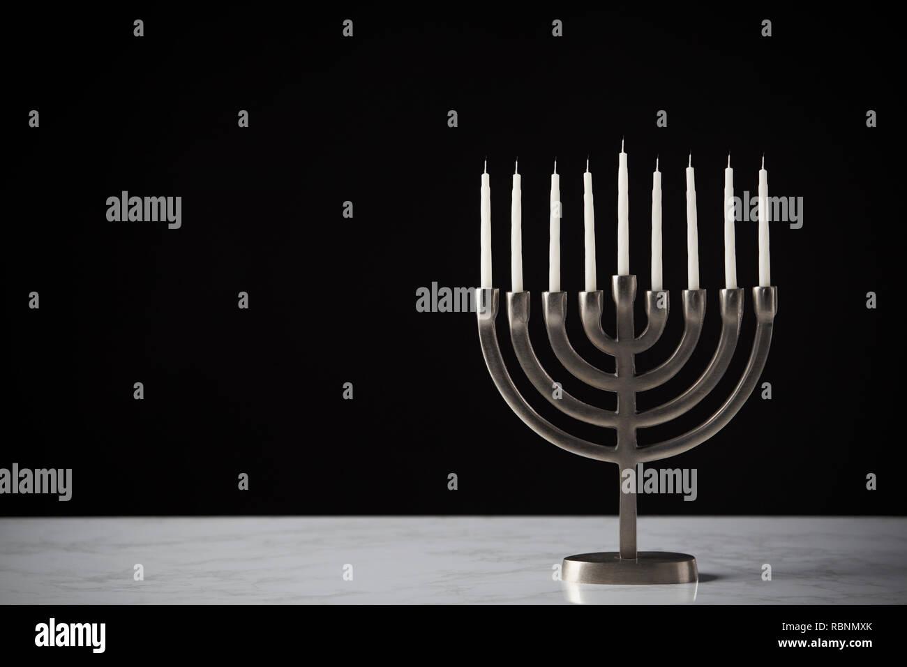 Metal Hanukkah Menorah With Unlit Candles On Marble Surface Against Black Studio Background - Stock Image