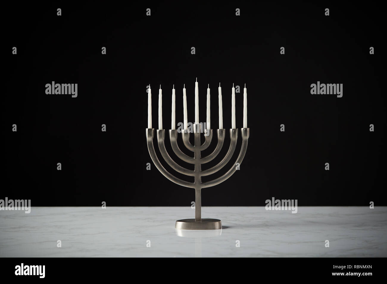 Metal Hanukkah Menorah With Unlit Candles On Marble Surface Against Black Studio Background - Stock Image