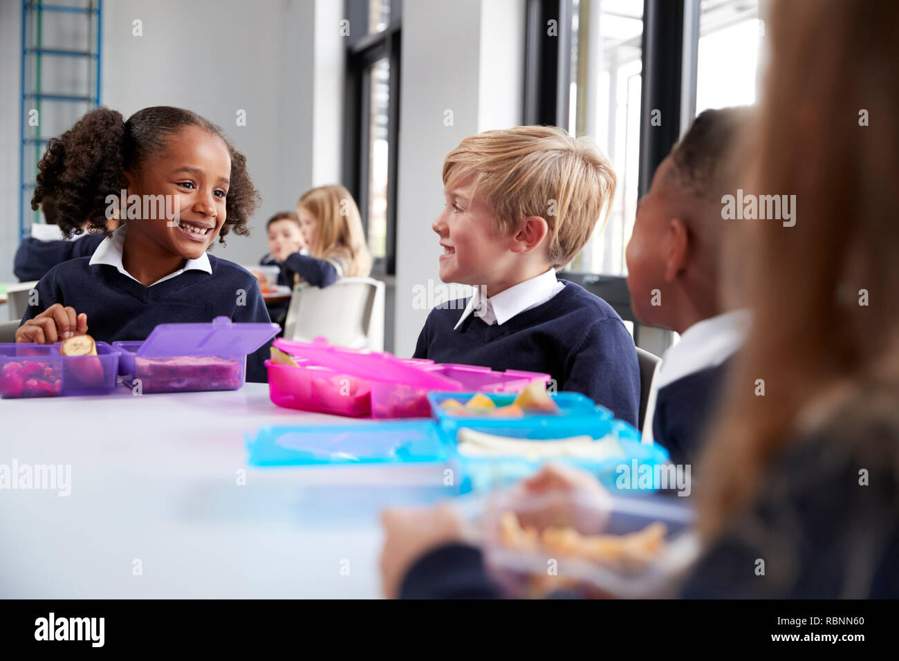 Primary school kids sitting at table eating their packed lunches and talking, close up - Stock Image