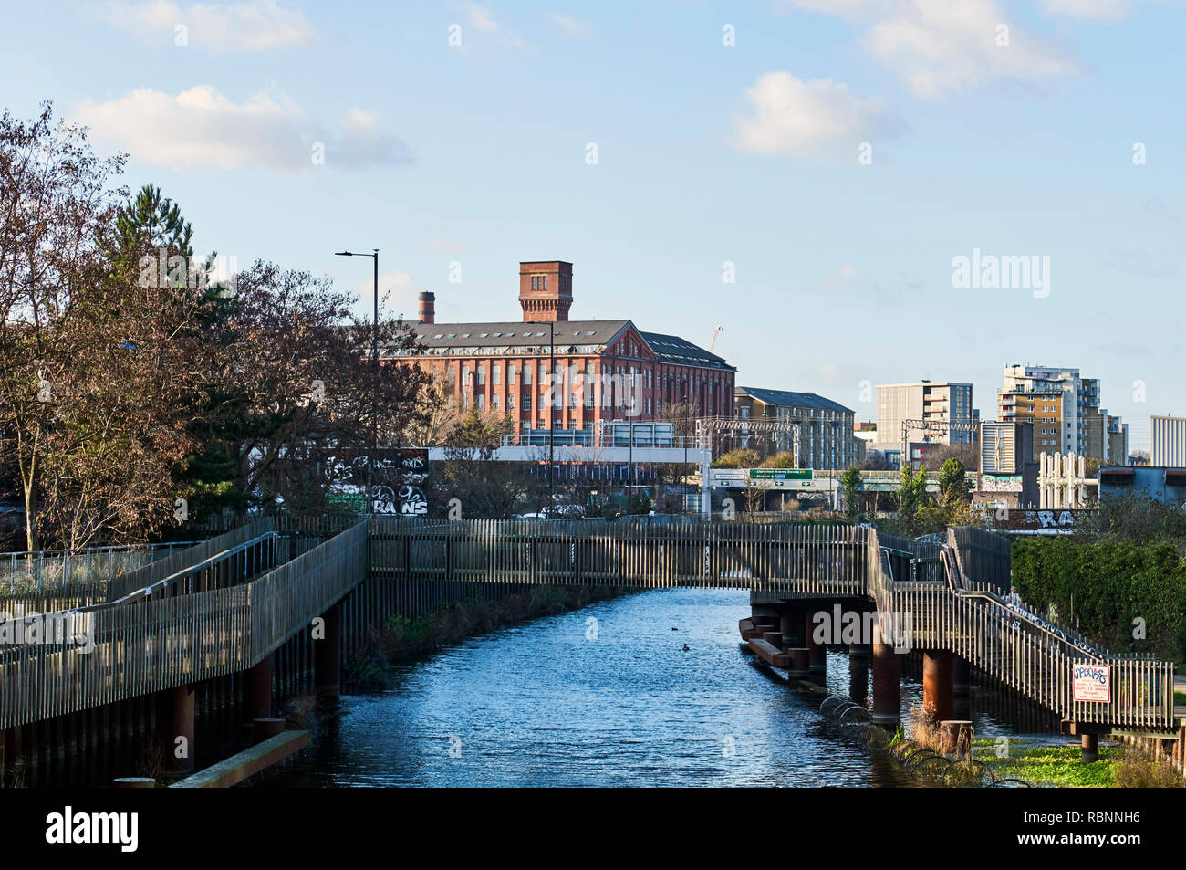 The River Lea and footbridge at Bow, East London UK, with the former Bryant & May match factory building in background - Stock Image
