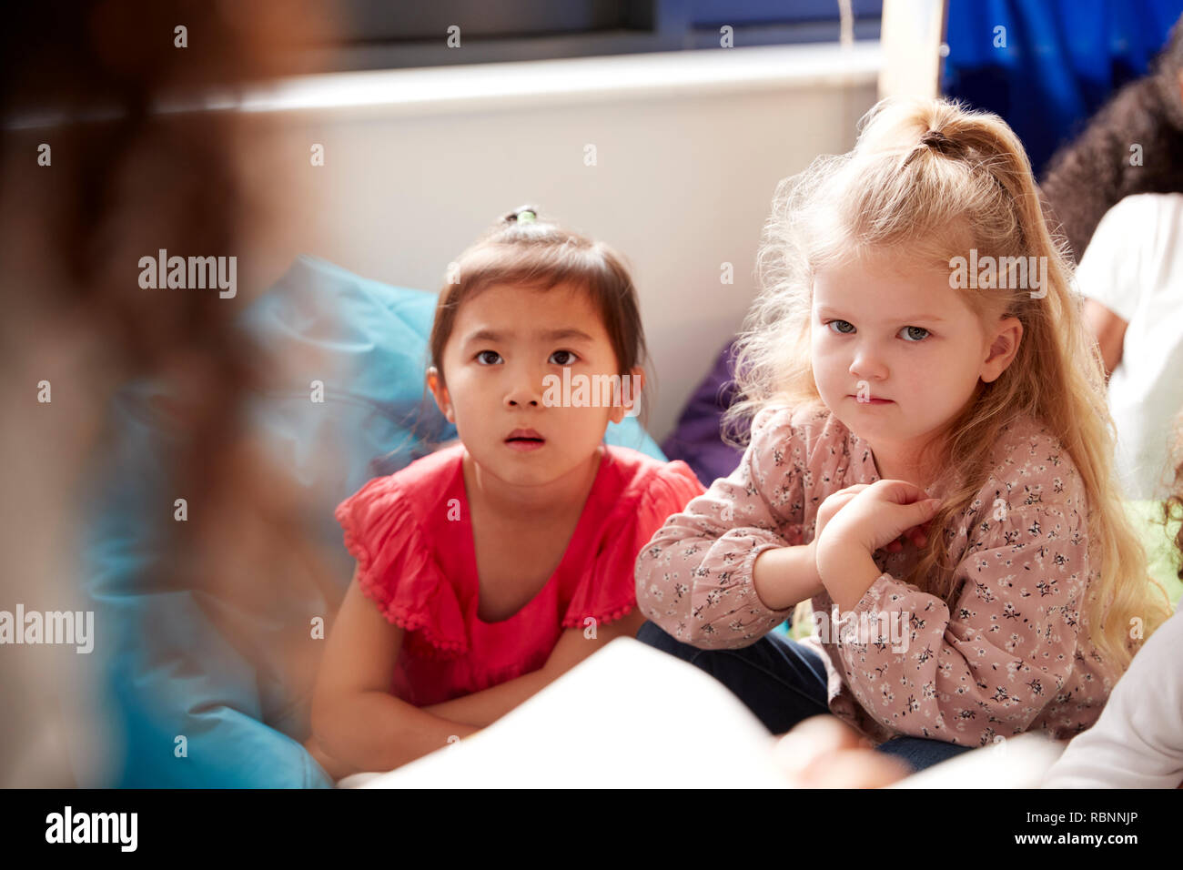 Two infant school girls sitting on bean bags in a comfortable corner of the classroom listening to their teacher reading a story, view over teacher's shoulder - Stock Image