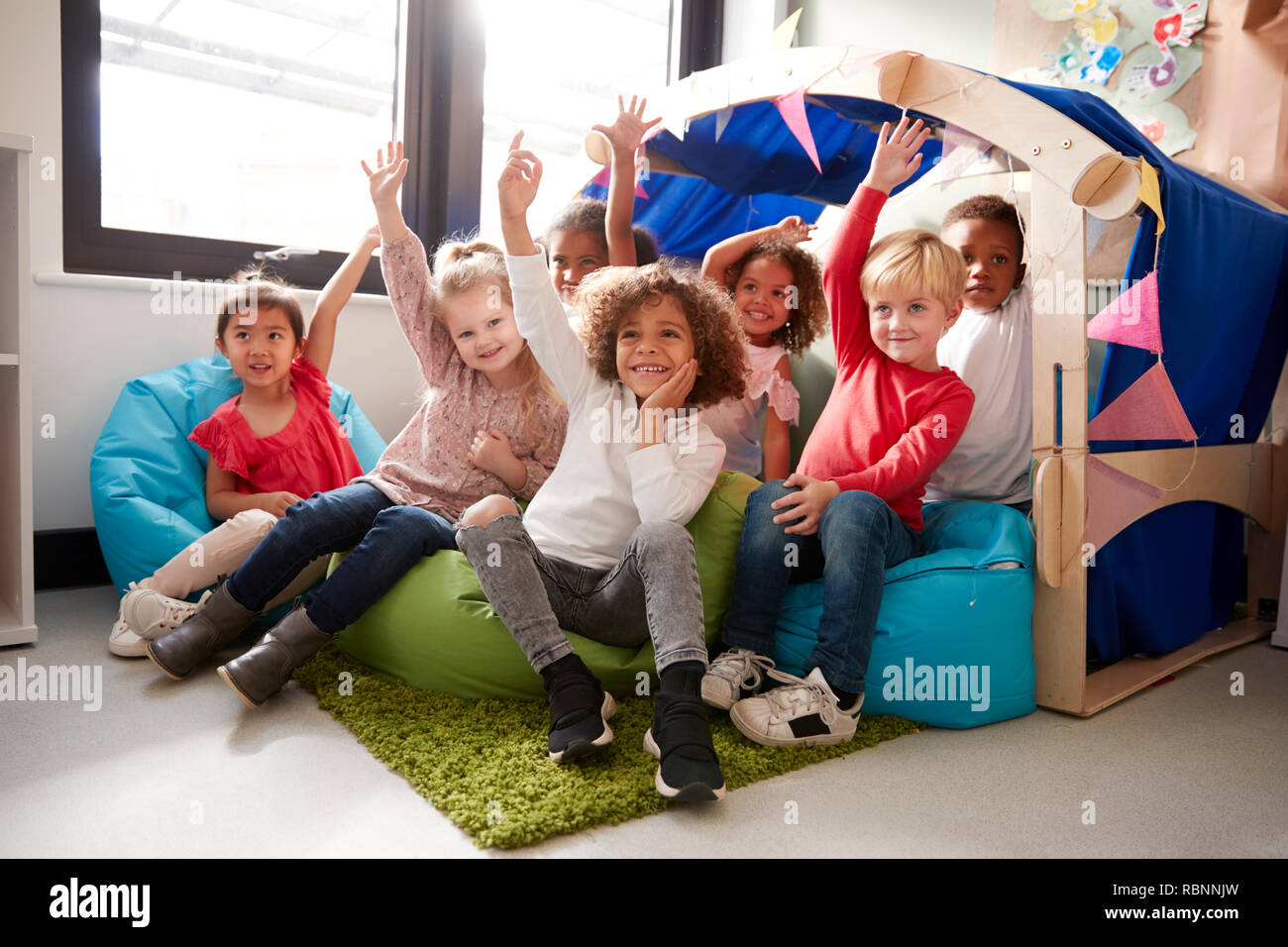 A multi-ethnic group of infant school children sitting on bean bags in a comfortable corner of the classroom, raising their hands to answer a question, low angle, close up - Stock Image