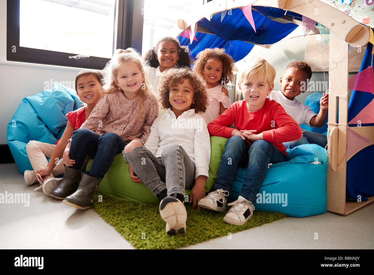 A multi-ethnic group of infant school children sitting on bean bags in a comfortable corner of the classroom, smiling to camera, low angle, close up - Stock Image