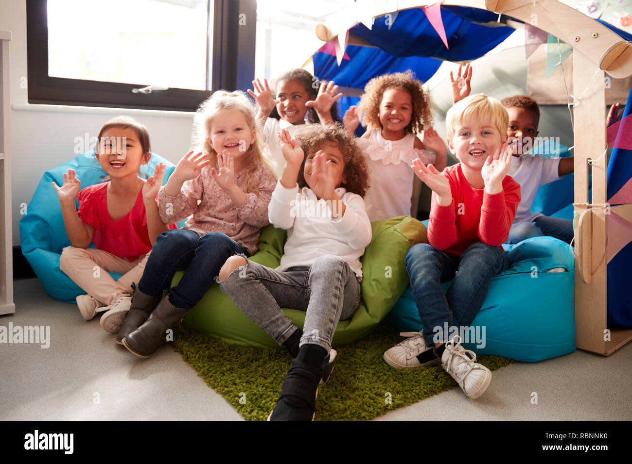A multi-ethnic group of infant school children sitting on bean bags in a comfortable corner of the classroom, smiling and waving to camera, low angle, close up - Stock Image
