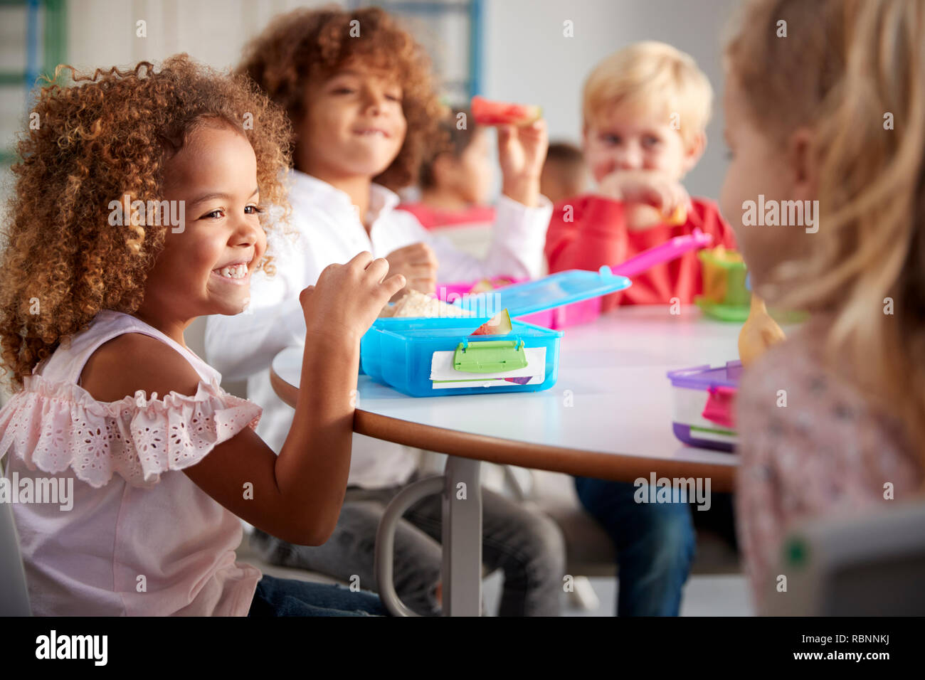 Close up of smiling young children sitting at a table eating their packed lunches together at infant school, selective focus Stock Photo