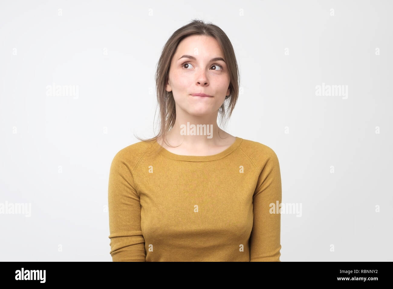 Young tricky woman having something in mind with sly facial expressions, over gray background - Stock Image