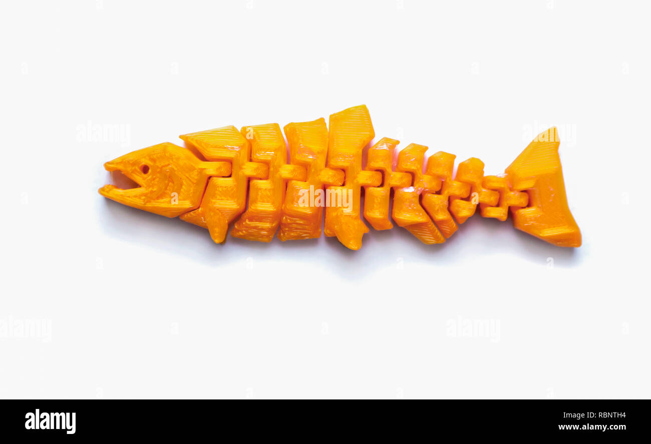 Bright light yellow object in shape of fishtoy printed on 3d printer isolated on white background. Fused deposition modeling, FDM. Concept modern progressive additive technology for 3d printing. - Stock Image