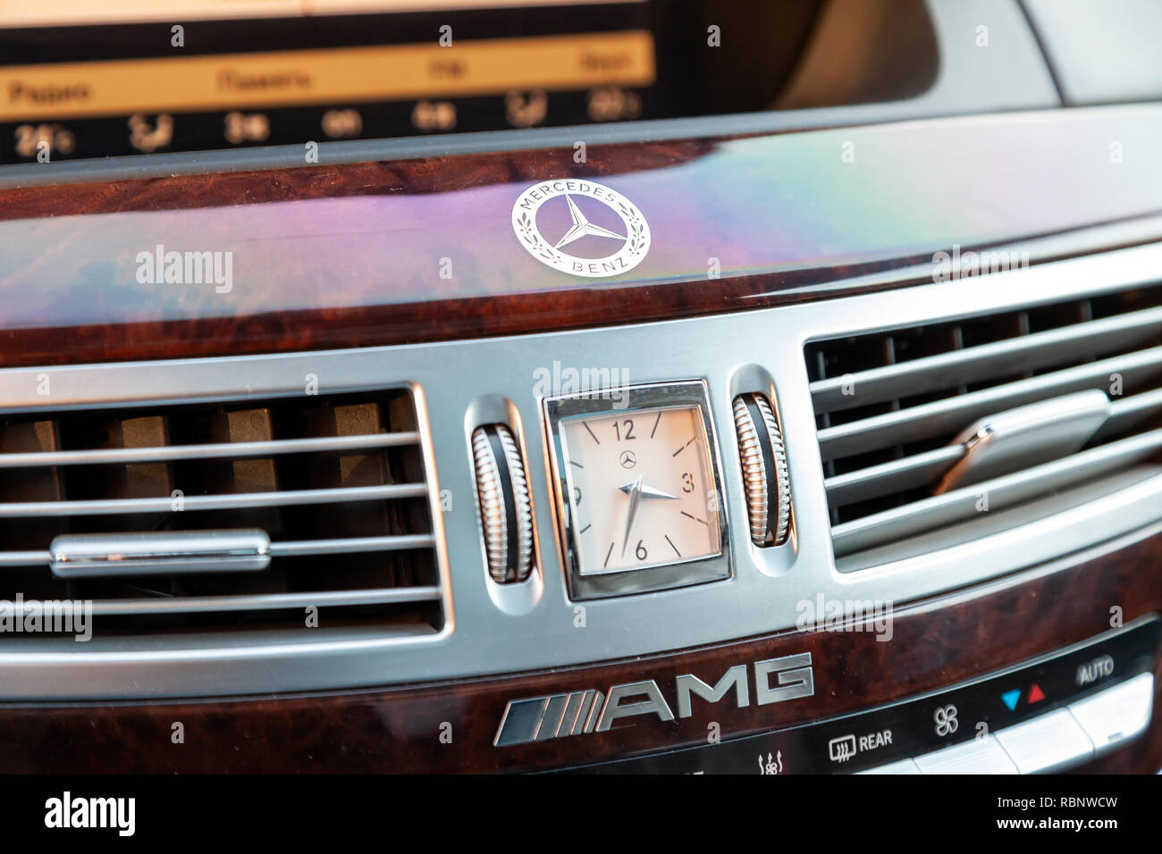Novosibirsk, Russia - 08.01.2018: The central control console in the interior of the car Mercedes Benz model AMG with a clock face on the panel and el - Stock Image