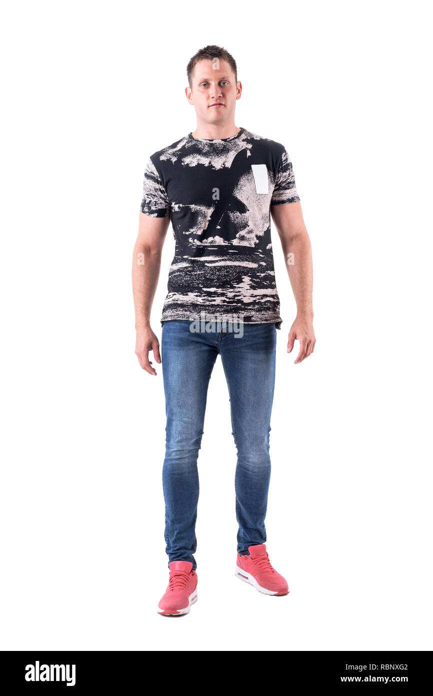 Confident serious young adult man looking at camera with arms down. Full body isolated on white background. - Stock Image