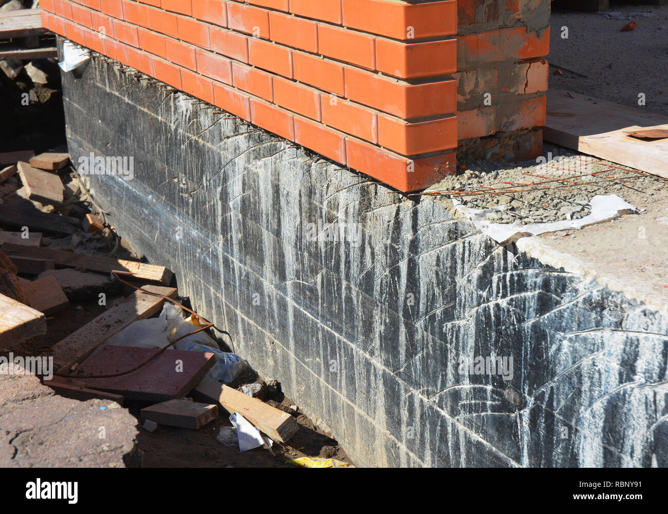Waterproofing foundation walls. Foundation Waterproofing and Damp proofing Coatings.Waterproofing house foundation with spray on tar. House insulation - Stock Image